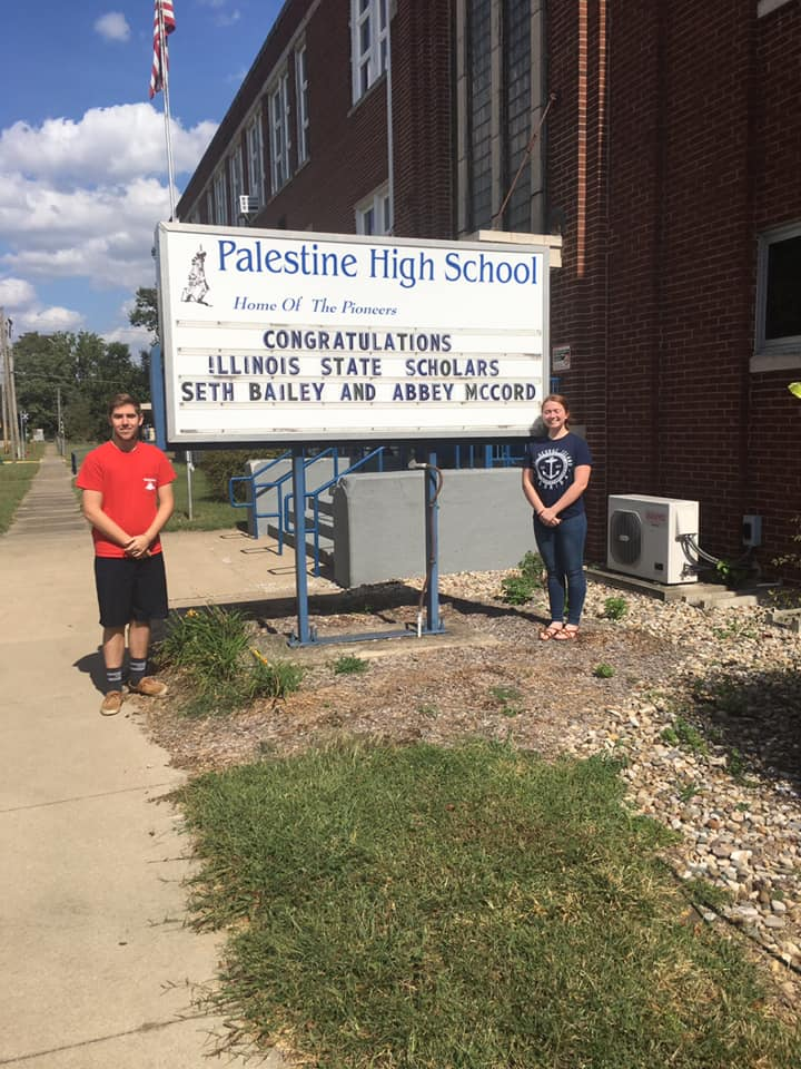 Seth Bailey and Abbey McCord, 2019 Illinois State Scholars, pose in front of the school sign announcing their awards.