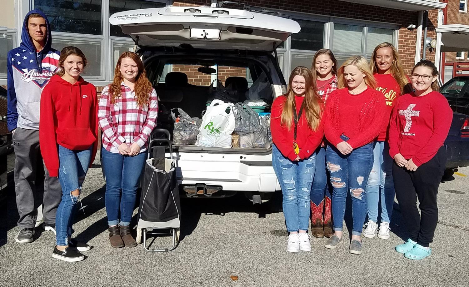 Pay It Forward members pose with canned items collected during the 2019 Trick or Treat for Cans Halloween night.
