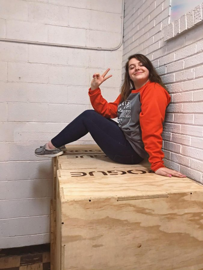 POSE! Layni Branson gets ready for her Senior So-long photo shoot. Layni has been hiding on these boxes in PE for four years.