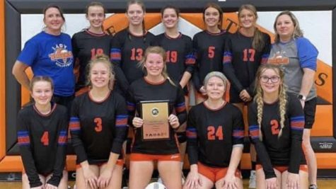 The varsity volleyball team holding their trophy after winning the LOVC tournament last weekend.